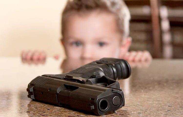 child looking at a gun